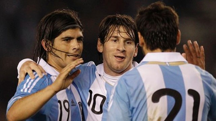 Argentina's Lionel Messi, center, celebrates with teammates Ezequiel Lavezzi, right, and Ever Banega after scoring against Albania at a friendly soccer match ahead of the upcoming 2011 Copa America in Buenos Aires, Argentina, Monday June 20, 2011. (AP Photo/Eduardo Di Baia)