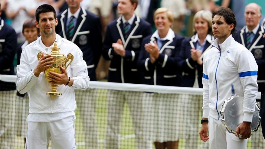 Serbia's Novak Djokovic, left, and Spain's Rafael Nadal hold their trophies after Novak Djokovic defeated Rafael Nadal in the men's singles final at the All England Lawn Tennis Championships at Wimbledon, Sunday, July 3, 2011. (AP Photo/Alastair Grant)