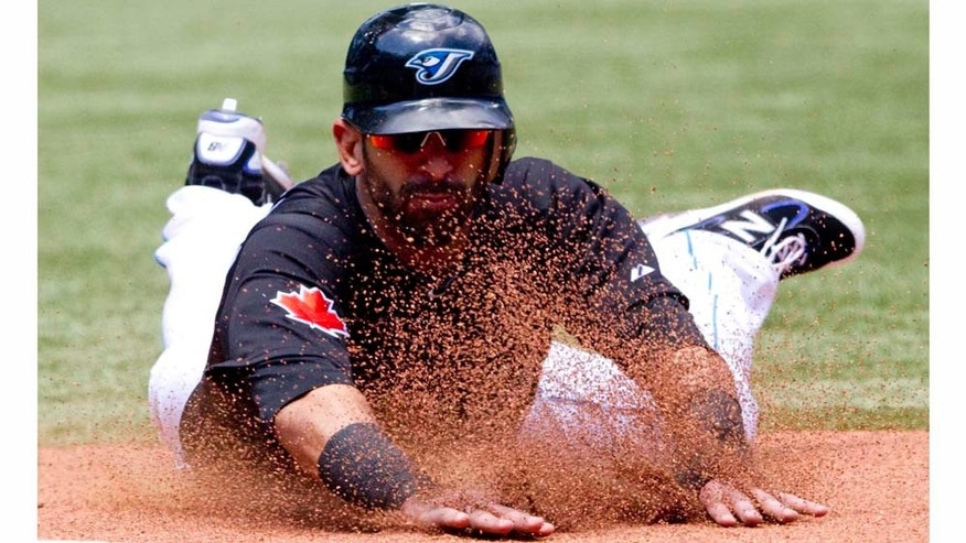 Toronto Blue Jays' Jose Bautista slides safely into third base during sixth inning of a baseball game against the Philadelphia Phillies, Sunday, July 3, 2011, in Toronto. The Blue Jays defeated the Phillies 7-4. (AP Photo/The Canadian Press, Darren Calabrese)