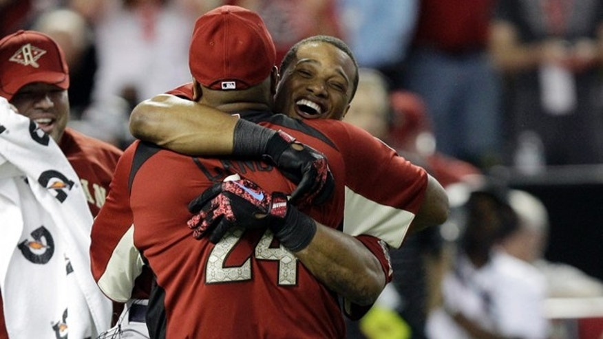 Jose Cano hugs his son American League's Robinson Cano of the New York Yankees after winning the MLB Home Run Derby Monday, July 11, 2011, in Phoenix. (AP Photo/David J. Phillip)