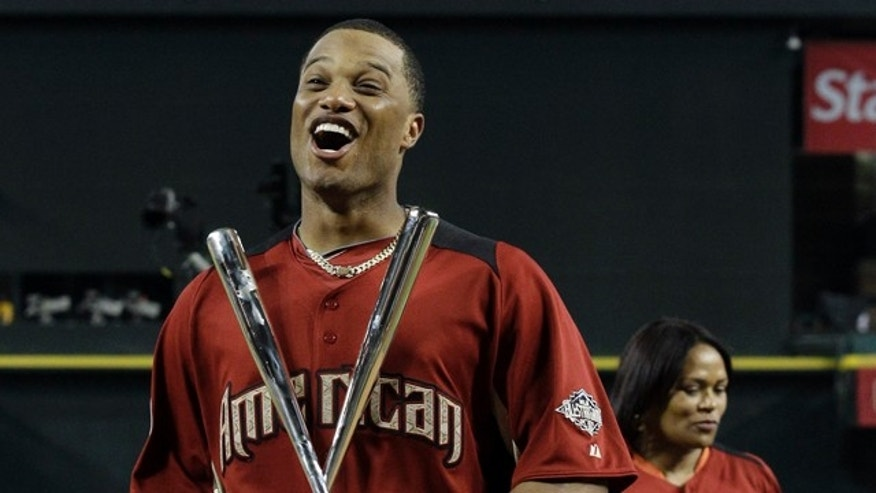 American League's Robinson Cano of the New York Yankees celebrates after winning the MLB Home Run Derby Monday, July 11, 2011, in Phoenix.  His mother Claribel Mercedes is in the background. (AP Photo/David J. Phillip)