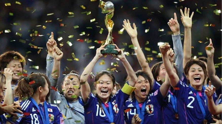 July 17: Japan players celebrate with the trophy after winning the final match between Japan and the United States at the Womens Soccer World Cup in Frankfurt, Germany. (AP Photo/Michael Probst)