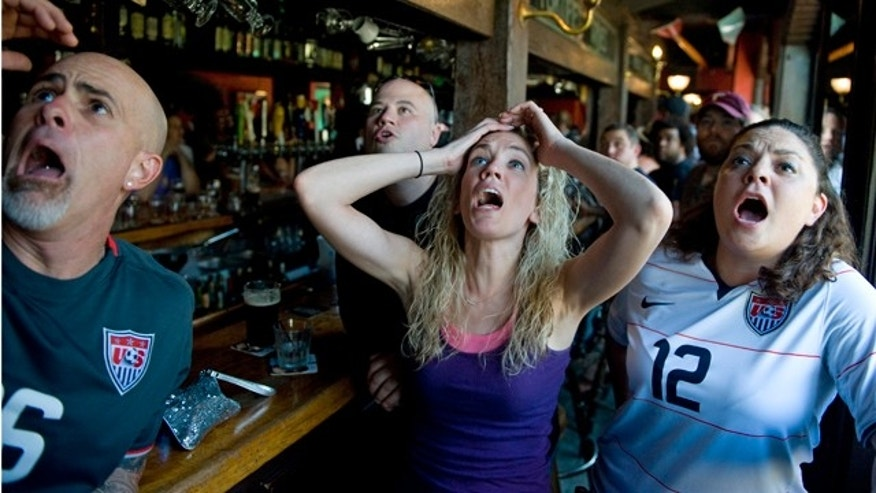Michael Giordano, left, Kate Giordano, center, Larry Derose, second from the left, and Michelle Bradley, react after watching the broadcast of the penalty kicks in the Women's World Cup soccer final between the United States and Japan, at Dark Horse Pub in Philadelphia. Japan won the title. (AP Photo/Courier-Post, Jose F. Moreno) MANDATORY CREDIT  NO SALES
