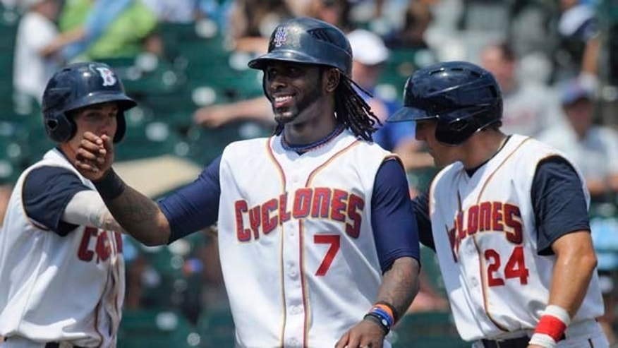 New York Mets' Jose Reyes, center, is greeted by teammates, including Cole Frenzel, right, after scoring the first run for the Brooklyn Cyclones in their baseball game against the Lowell Spinners in the New York City borough of Brooklyn, Monday, July 18, 2011. Frenzel also scored on the play.  Reyes made a rehabilitation start for Class-A Brooklyn. (AP Photo/Henny Ray Abrams)