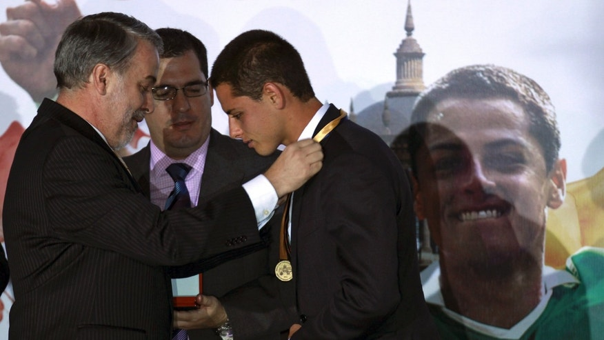 "Mexican soccer player Javier ""Chicharito"" Hernandez, right, is awarded a medal from the governor of the state of Jalisco, Emilio Gonzalez Marquez,  during a ceremony in which Chicharito was named the 2011 Tourism Ambassador for the State of Jalisco, in Guadalajara, Mexico Thursday July 21, 2011. Chicharito  currently plays for the  English football club Manchester United. (AP Photo/Bruno Gonzalez)"