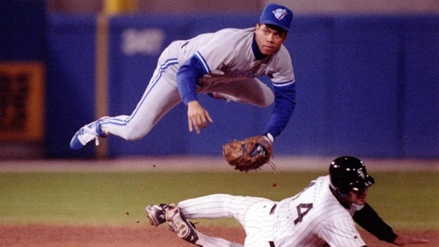 Oct 5, 1993: Roberto Alomar of the Toronto Blue Jays goes airbourne over Chicago White Sox Dan Pasqua to convert the double play. (Jonathan Daniel/ALLSPORT)