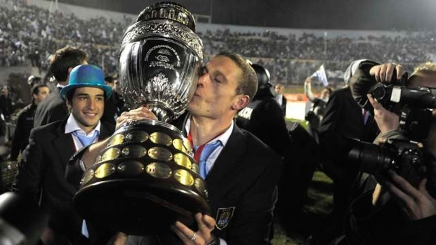 Uruguay's Diego Perez kisses the trophy as the team celebrates in the Centenario Stadium in Montevideo, Uruguay Monday July 25, 2011. Uruguay won the Copa America for a record 15th time after beating Paraguay 3-0 in Argentina Sunday. (AP Photo/Andres Cuenca)  (AP Photo/Matilde Campodonico)