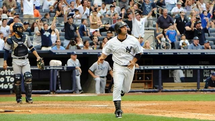 New York Yankees' Jorge Posdada, center, watches his grand slam during the fifth inning of a baseball game against the Tampa Bay Rays, Saturday, Aug. 13, 2011, at Yankee Stadium in New York. (AP Photo/Bill Kostroun)