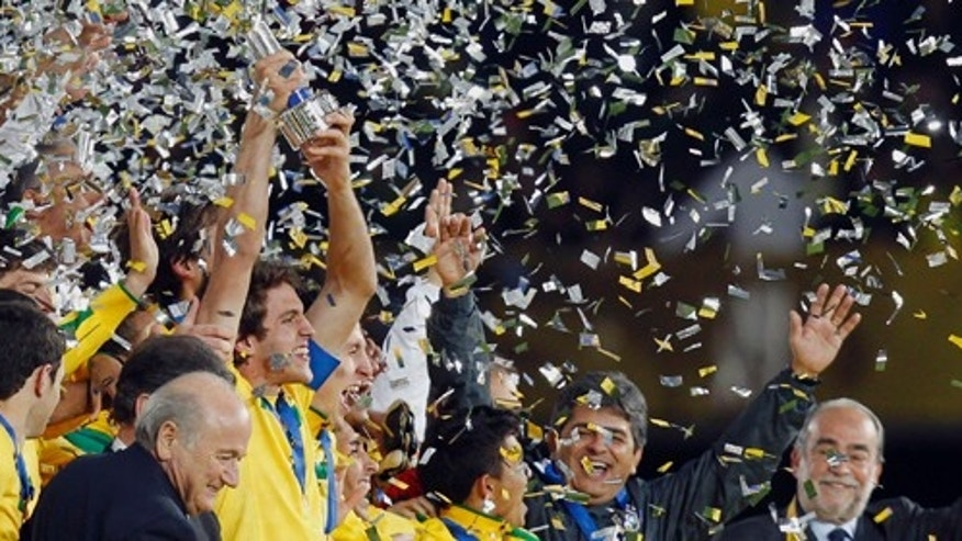 Brazil's Bruno Uvini holds up his team's U-20 World Cup trophy after the final soccer match between the Brazil and Portugal in Bogota, Colombia, Saturday Aug. 20, 2011. Brazil defeated Portugal 3-2 on extra time and won the U-20 World Cup championship. At front left is FIFA President Sepp Blatter.  (AP Photo/Ricardo Mazalan)