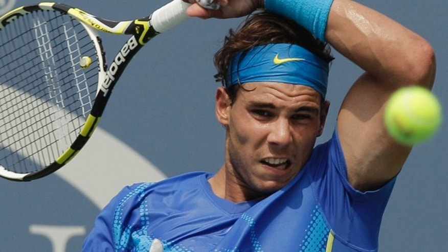 Rafael Nadal of Spain returns a shot to David Nalbandian of Argentina during the U.S. Open tennis tournament in New York, Sunday, Sept. 4, 2011. (AP Photo/Charlie Riedel)