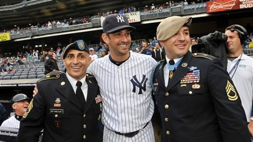 Sept 7: New York Yankees' Jorge Posada greets U.S. Army Sgt. Al Betancourt, left, and Congressional Medal of Honor awardee Sgt. 1st Class Leroy Petry before ceremonies to honor the 10-year anniversary of September 11, 2001