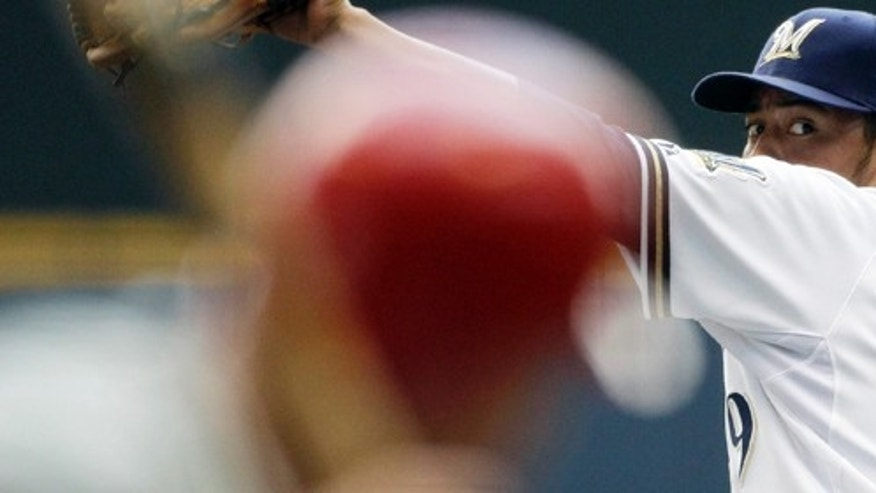 Milwaukee Brewers starting pitcher Yovani Gallardo throws to Philadelphia Phillies' Hunter Pence during the first inning of a baseball game, Sunday, Sept. 11, 2011, in Milwaukee. (AP Photo/Morry Gash)