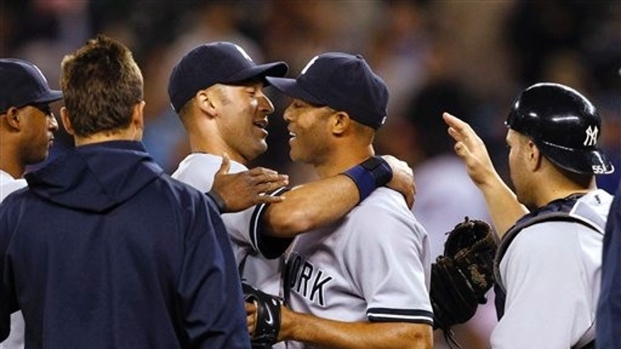 Sept 13: New York Yankees closer Mariano Rivera, center, is greeted by Derek Jeter and other teammates after the team beat the Seattle Mariners.