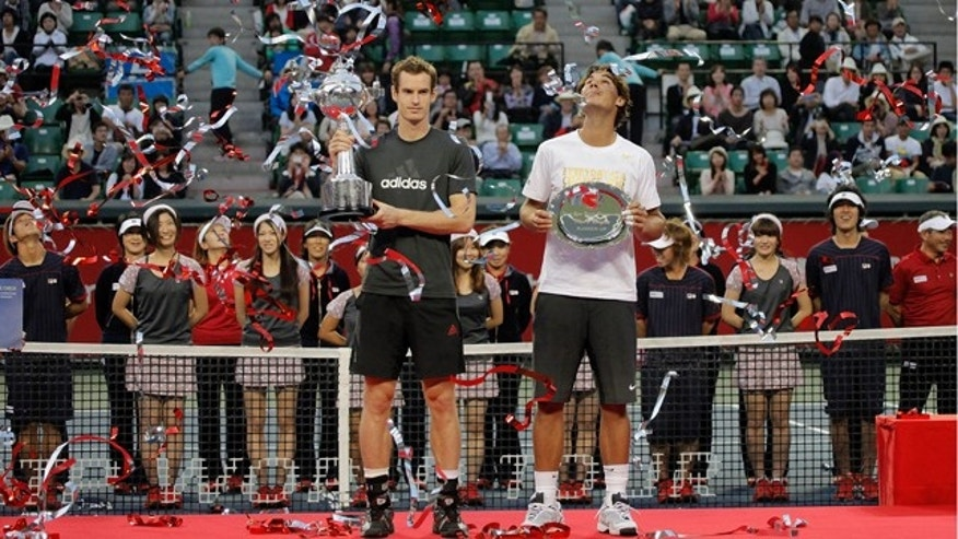 Andy Murray of Britain, center left, shows his trophy he won after beating Rafael Nadal of Spain in their final match at the Japan Open tennis tournament in Tokyo, Japan, Sunday, Oct. 9, 2011. Andy Murray won, 3-6, 6-2, 6-0. (AP Photo/Itsuo Inouye)