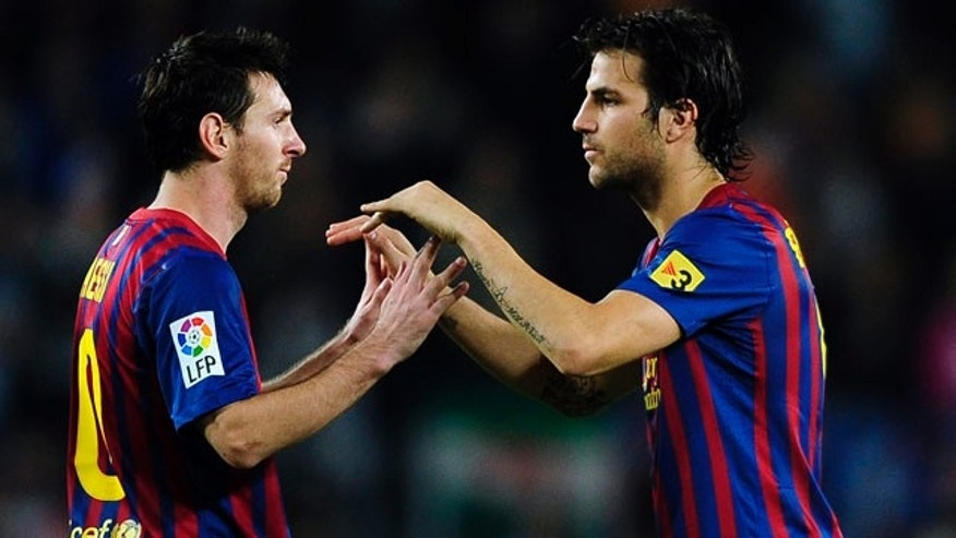 FC Barcelona's Lionel Messi, from Argentina, left, and Cesc Fabregas, right, react during a Spanish La Liga soccer match against Sevilla at the Camp Nou stadium in Barcelona, Spain, Saturday, Oct. 22, 2011. (AP Photo/Manu Fernandez)