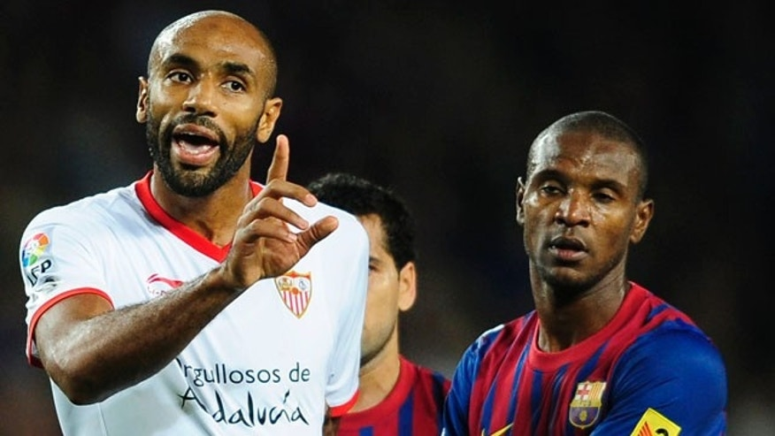 Sevilla's Frederic Kanoute, left, argues with FC Barcelona players during a Spanish La Liga soccer match against FC Barcelona at the Camp Nou stadium in Barcelona, Spain, Saturday, Oct. 22, 2011. (AP Photo/Manu Fernandez)