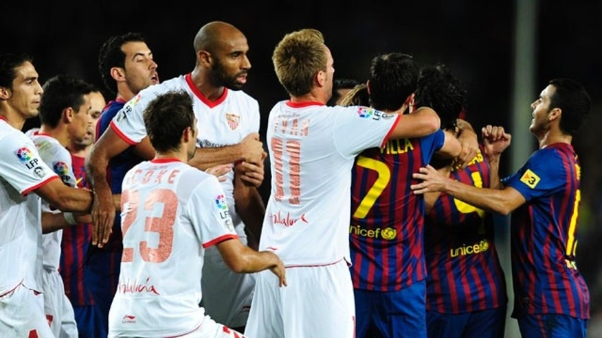 Sevilla's Frederic Kanoute, center left, argues with FC Barcelona's Cesc Fabregas, second right, during a Spanish La Liga soccer match against FC Barcelona at the Camp Nou stadium in Barcelona, Spain, Saturday, Oct. 22, 2011. (AP Photo/Manu Fernandez)
