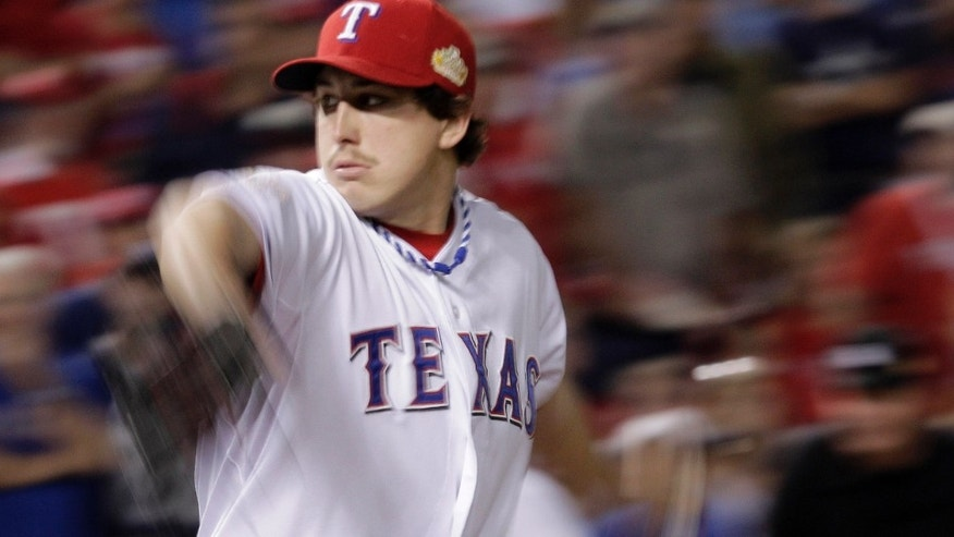 Texas Rangers starting pitcher Derek Holland throws during the ninth inning of Game 4 of baseball's World Series against the St. Louis Cardinals Sunday, Oct. 23, 2011, in Arlington, Texas. (AP Photo/Charlie Riedel)