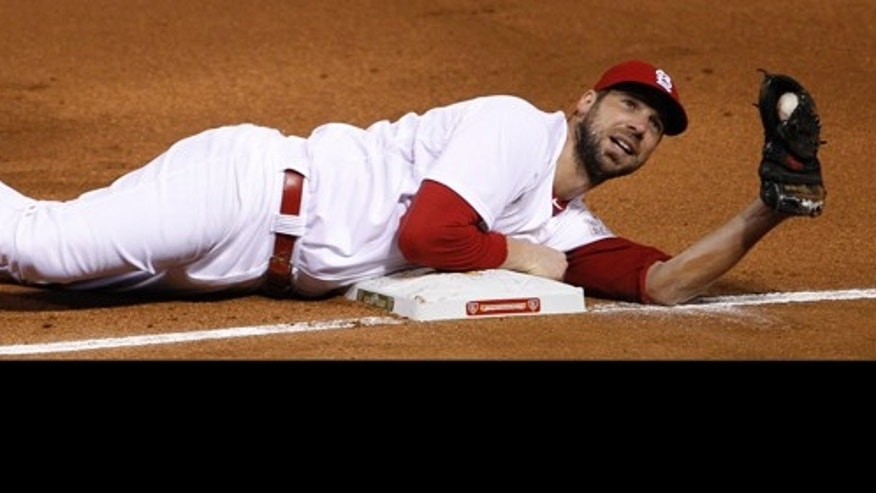 St. Louis Cardinals starting pitcher Chris Carpenter looks up after diving to tag first base to get Texas Rangers' Elvis Andrus out during the first inning of Game 1 of baseball's World Series Wednesday, Oct. 19, 2011, in St. Louis. (AP Photo/Eric Gay)