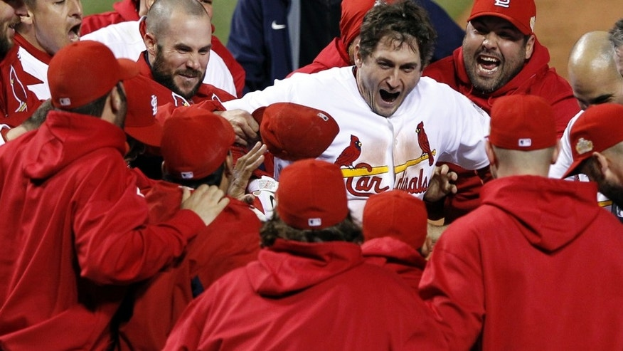 Teammates celebrate with St. Louis Cardinals' David Freese after Freese hit a walk-off home run during the 11th inning of Game 6 of baseball's World Series against the Texas Rangers Thursday, Oct. 27, 2011, in St. Louis. The Cardinals won the game 10-9 to tie the series 3-3. (AP Photo/Eric Gay)