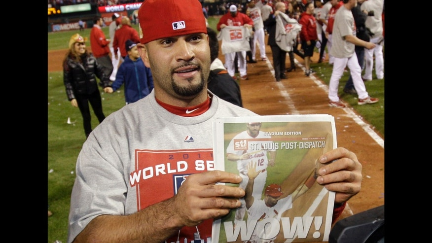 St. Louis Cardinals' Albert Pujols holds up a newspaper after Game 7 of baseball's World Series against the Texas Rangers Friday, Oct. 28, 2011, in St. Louis. The Cardinals won 6-2 to win the series.  (AP Photo/Matt Slocum)