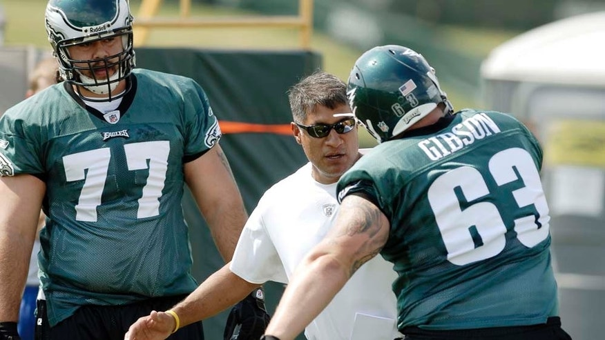 FILE - In this July 25, 2008, file photo, Philadelphia Eagles offensive line coach Juan Castillo, center, gives directions to defensive end Mike Gibson, right, during the NFL football team's training camp in Bethlehem, Pa. At left is offensive lineman Cameron Stephenson. Castillo, who spent 13 seasons as offensive line coach and has been with the organization for 16 years, will switch over to the defensive side of the ball, and replace Sean McDermott, who was fired on Jan. 15. (AP Photo/Bradley C Bower, File)