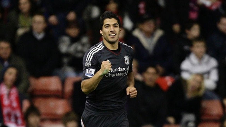 Liverpool's Luis Suarez celebrates after scoring during his team's 2-1 victory over Stoke in their English League Cup soccer match at the Britannia Stadium, Stoke, England, Wednesday Oct. 26, 2011. (AP Photo/Jon Super)