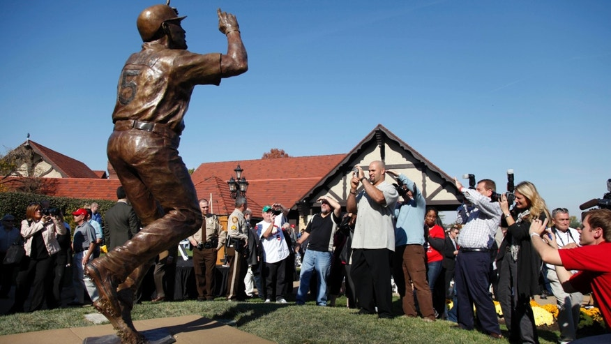 Baseball player Albert Pujols, front,  stands with other photographers as he takes a picture of a 10-foot, 1,100-pound bronze statue of the St. Louis Cardinals slugger after its dedication Wednesday, Nov. 2, 2011, in Maryland Heights, Mo. (AP Photo/Jeff Roberson)