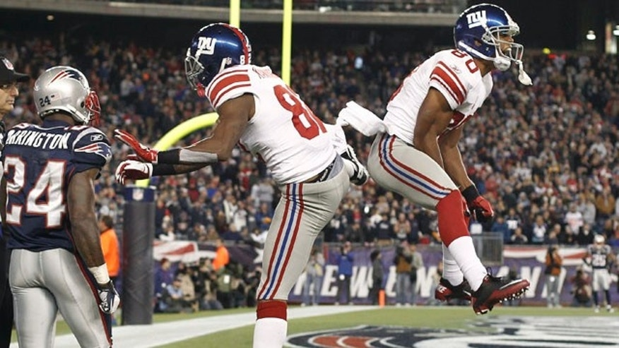 New York Giants wide receiver Mario Manningham, center, celebrates his touchdown with wide receiver Victor Cruz, right, as New England Patriots defensive back Kyle Arrington watches in the fourth quarter of an NFL football game in Foxborough, Mass., Sunday, Nov. 6, 2011. (AP Photo/Winslow Townson)