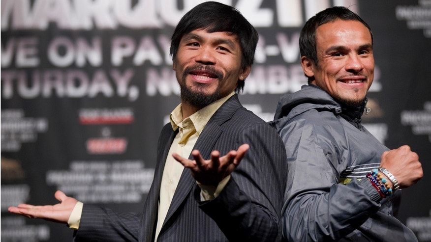 Manny Pacquiao, left, jokes with members of the media while posing for photos with Juan Manuel Marquez during a news conference Wednesday, Nov. 9, 2011, in Las Vegas. Pacquiao and Marquez are scheduled to meet for boxing's WBO welterweight title on Saturday. (AP Photo/Julie Jacobson)