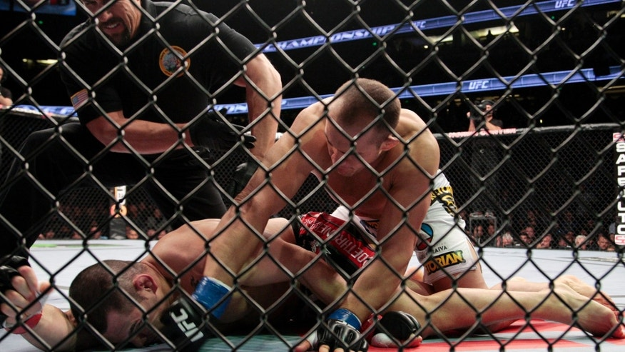 Junior dos Santos, top right, of Brazil, takes down Cain Velasquez as an official moves in to stop the fight in the UFC mixed martial arts heavyweight title bout in Anaheim, Calif., Saturday, Nov. 12, 2011. Dos Santos won by knockout in the first round. (AP Photo/Jason Redmond)