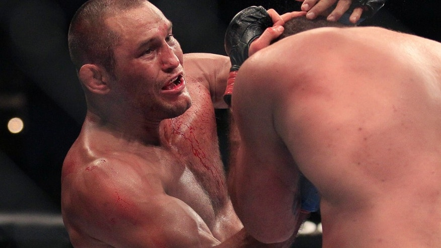 Dan Henderson, top, punches Mauricio Rua, from Brazil, during the second round of a UFC 139 Mixed Martial Arts light heavyweight bout in San Jose, Calif., Saturday, Nov. 19, 2011. Henderson won by unanimous decision. (AP Photo/Jeff Chiu)