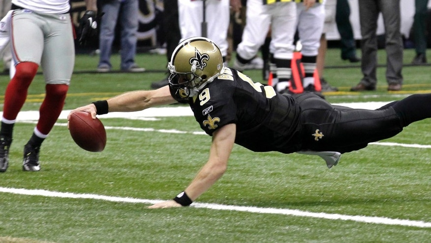 New Orleans Saints quarterback Drew Brees (9) dives into the end zone for a touchdown during the third quarter of an NFL football game against the New York Giants in New Orleans, Monday, Nov. 28, 2011. (AP Photo/Bill Haber)