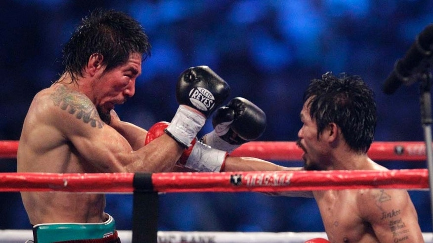 Manny Pacquiao, right, hits Antonio Margarito during the 12th round of their WBC light middleweight title boxing match Saturday, Nov. 13, 2010, in Arlington, Texas. (AP Photo/LM Otero)