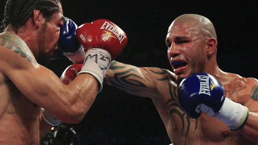 Miguel Cotto, of Puerto Rico,  punches Antonio Margarito, of Mexico,  during the eighth round of an WBA World Junior Middleweight Championship boxing matchCotto defeated Margarito with a TKO decision amid confusion in the corner before they came out for the 10th round. (AP Photo/Frank Franklin II)