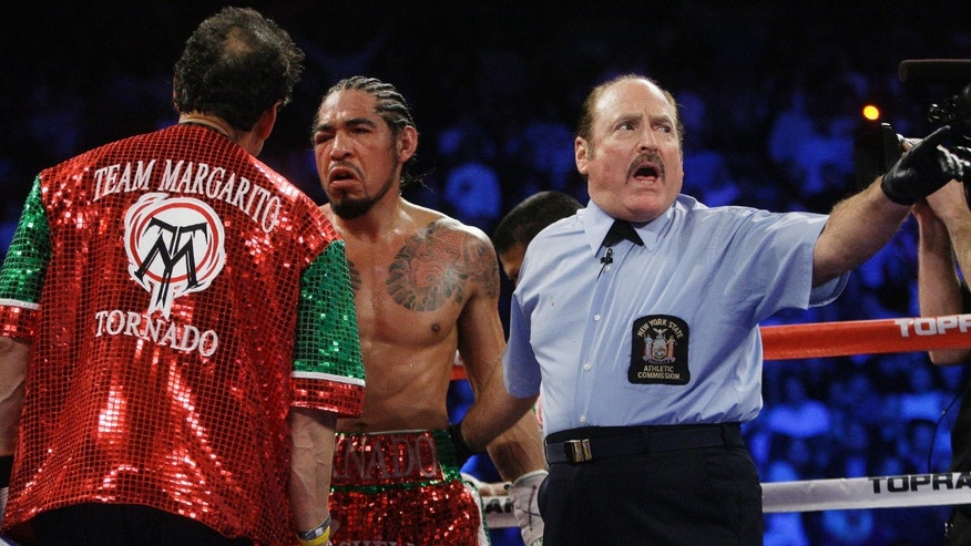 Antonio Margarito, of Mexico, reacts while talking to a trainer before the ninth round of an WBA World Junior Middleweight Championship boxing match against Miguel Cotto, of Puerto Rico, Sunday, Dec. 4, 2011  in New York. Cotto defeated Margarito with a TKO decision amid confusion in the corner before they came out for the 10th round. (AP Photo/Frank Franklin II)