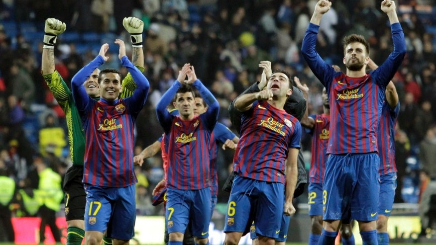 FC Barcelona's players celebrates their victory during the Spanish La Liga soccer match against Real Madrid at the Santiago Bernabeu stadium in Madrid, Spain, Saturday, Dec. 10, 2011. (AP Photo/Andres Kudacki)