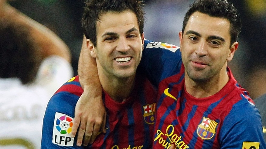 FC Barcelona's Cesc Fabregas, center, celebrates with Xavi Hernandez, right, during the Spanish La Liga soccer match against Real Madrid at the Santiago Bernabeu stadium in Madrid, Spain, Saturday, Dec. 10, 2011. (AP Photo/Andres Kudacki)