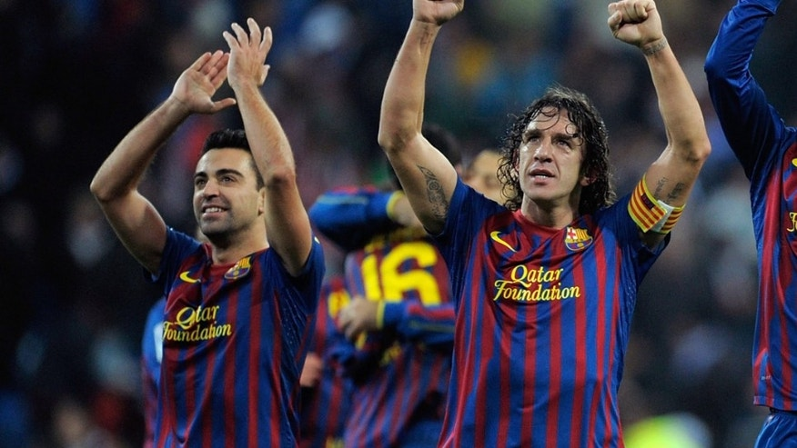 MADRID, SPAIN - DECEMBER 10: Carles Puyol (C) Javi Hernandez (L) and Gerard Pique celebrate after Barcelona beat Real Madrid 3-1 during the La Liga match between Real Madrid and Barcelona at Estadio Santiago Bernabeu on December 10, 2011 in Madrid, Spain.  (Photo by Denis Doyle/Getty Images)
