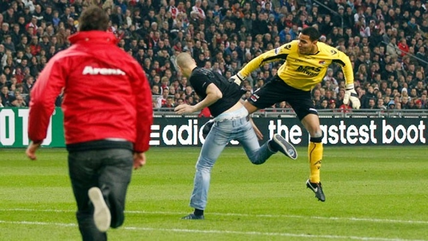 Dec. 21, 2011: Keeper Esteban Alvarado, right, defends himself against an attacker who rushed from the stands as referee Bas Nijhuis, left, runs towards them during a cup match between Ajax and AZ Alkmaar in Amsterdam, Netherlands.