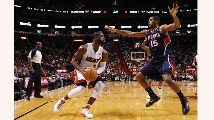 Miami Heat's Dwyane Wade (3) looks to pass as Atlanta Hawks' Al Horford (15) defends during the first half of an NBA basketball game, Monday, Jan. 2, 2012, in Miami. (AP Photo/Lynne Sladky)