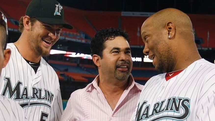 New Florida Marlins manager Ozzie Guillen, center, talks with Marlins pitcher Josh Johnson, left, and former pitcher Livian Hernandez (61) following the Marlins' baseball game against the Washington Nationals in Miami, Wednesday, Sept. 28, 2011. The Marlins played their last game at Sun Life Stadium and had a post-game ceremony honoring past players. They move to a new ballpark in 2012. (AP Photo/Lynne Sladky)