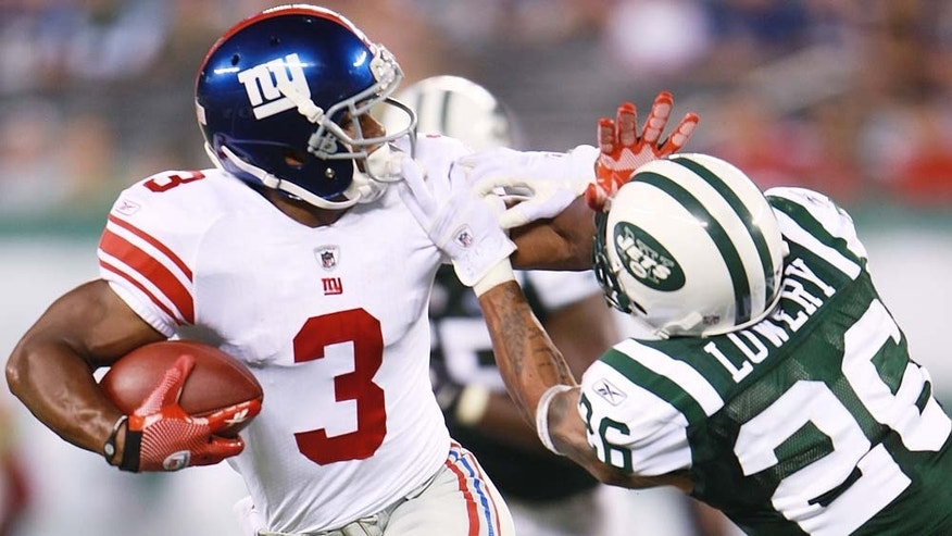 New York Giants Victor Cruz fights off Jets defender.