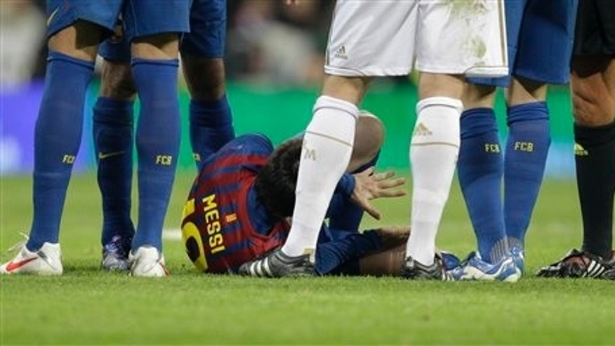 FC Barcelona's Lionel Messi from Argentina, lies on the ground holding his hand after Real Madrid's Pepe of Portugal stomped on it during a Copa del Rey quarter final, 1st leg soccer match against Real Madrid at the Bernabeu stadium in Madrid Wednesday Jan. 18, 2012.