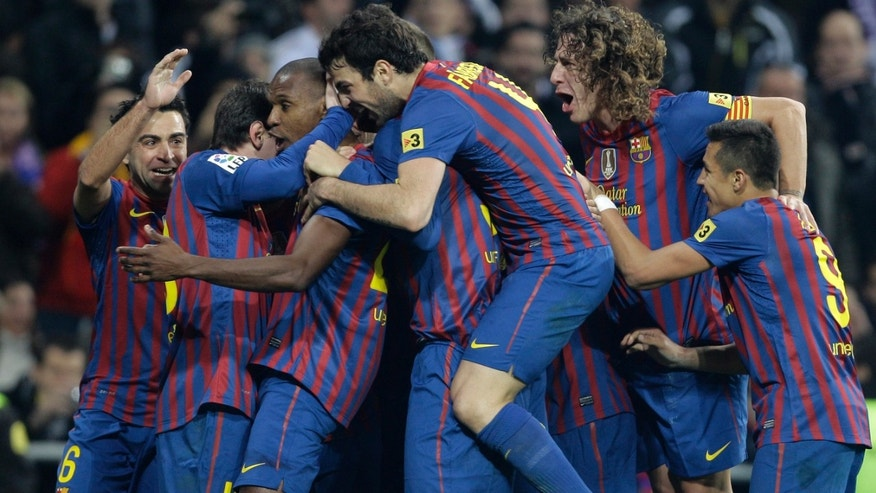 FC Barcelona's  Eric Abidal, from France, 3rd from left celebrates with various teammates after scoring the winning goal against Real Madrid during a Copa del Rey quarter final, 1st leg soccer match at the Bernabeu stadium in Madrid Wednesday, Jan. 18, 2012. Barcelona won the match 2-1. (AP Photo/Paul White)