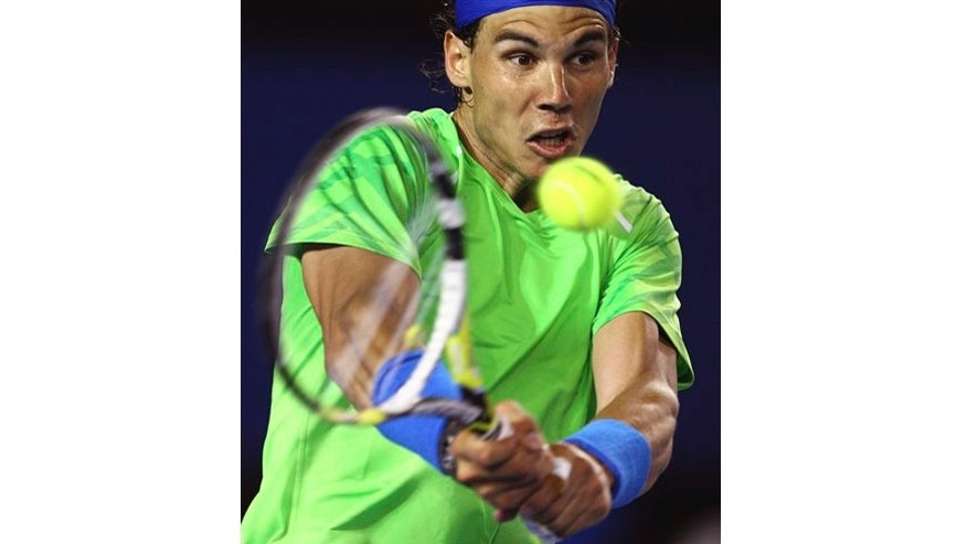 Rafael Nadal of Spain hits a backhand return to Tomas Berdych of the Czech Republic during their quarterfinal at the Australian Open tennis championship, in Melbourne, Australia, Tuesday, Jan. 24, 2012.(AP Photo/Rick Rycroft)