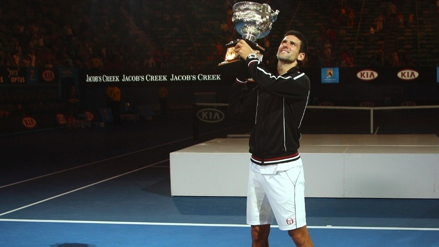 Novak Djokovic of Serbia holds the trophy aloft  during the awarding ceremony after defeating Rafael Nadal of Spain in the men's singles final at the Australian Open tennis championship, in Melbourne, Australia, early Monday, Jan. 30, 2012. (AP Photo/Rick Rycroft)
