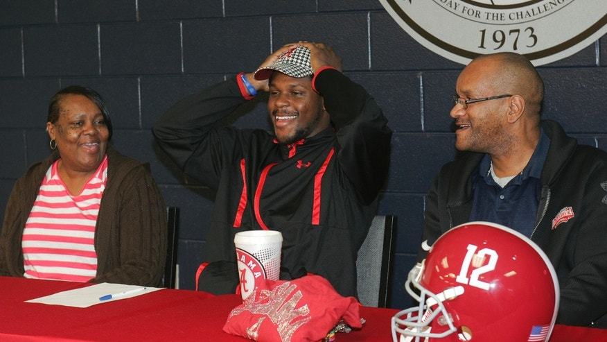 Bob Jones High School football player Reggie Ragland puts on an Alabama hat as mom Ann White and dad Reggie Ragland Sr., look on, after announcing his intentions to attend the University of Alabama and play football during national signing day, Wednesday, Feb. 1, 2012, at Bob Jones High School in Madison, Ala. (AP Photo/The Huntsville Times, Robin Conn)
