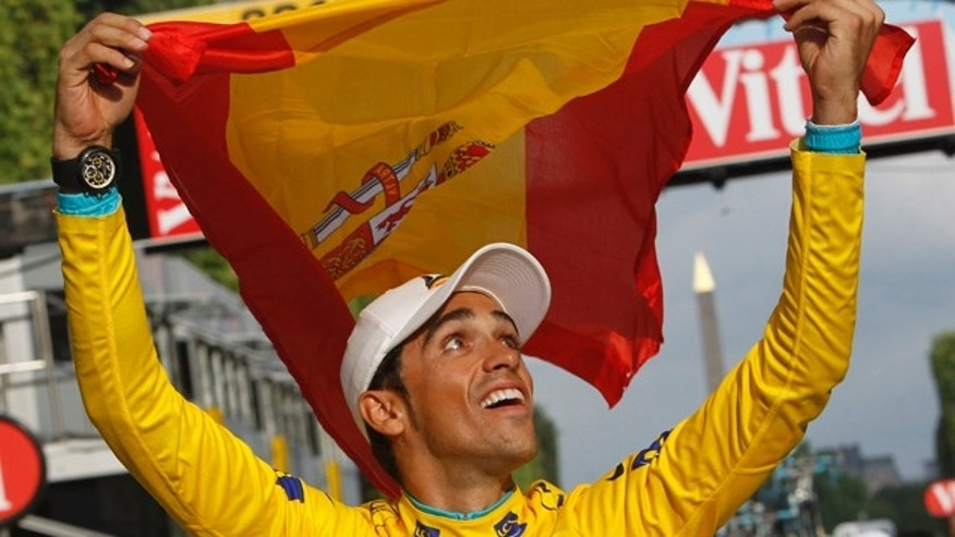 July 25, 2010: FILE - In this file photo,  three-time Tour de France winner Alberto Contador of Spain holds aloft the Spanish national flag during a victory lap  after winning the Tour de France cycling race in Paris.
