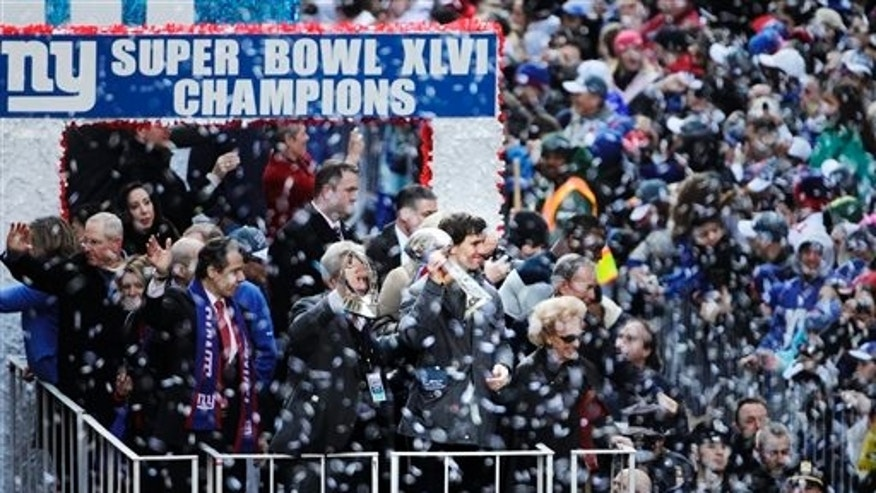 Feb. 7, 2012: New York Giants' Eli Manning, second from right, holds up the Vince Lombardi trophy as a float makes its way up Broadway in New York. Joining Manning are New York Gov. Andrew Cuomo, left, and Giants chairman Steve Tisch, center, holding the Halas Trophy.